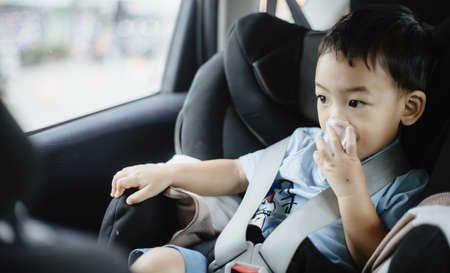 1 Year Old Adorable Asian Boy Alone Looking Around From Car Seat in the Car Portrait. Family Trips and Baby Care and Safety Concept. Front View Headshot CloseUp Copy Space, and Blurry Background.