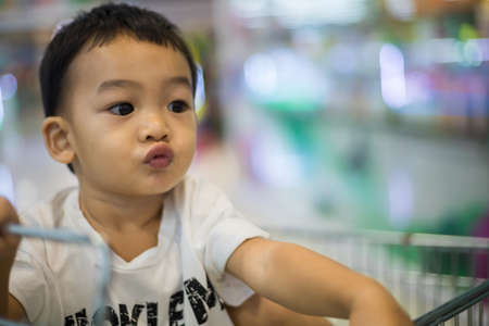 An Adorable toddler Asian boy (1-year-old) sitting and play inside the trolley with blurry supermarket background. Children's portrait on safety play space. Kid activity and family's lifestyle ideas. Standard-Bild