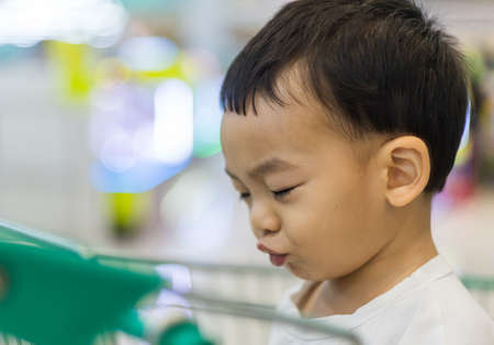 An Adorable toddler Asian boy (1-year-old) sitting and play inside the trolley with blurry supermarket background. Children's portrait on safety play space. Kid activity and family's lifestyle ideas.