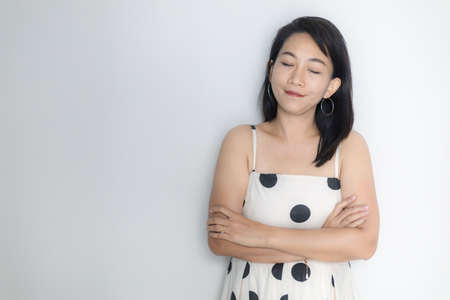 Portrait of beautiful adult (40 years old) Asian woman in polka dots dress with arms crossed and pretending closing eyes over isolated white background. People's body authentic and feeling concept. 스톡 콘텐츠