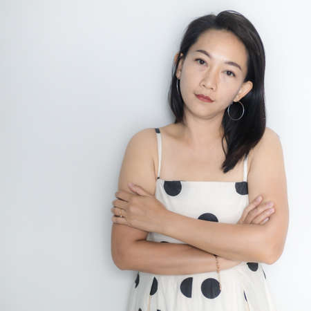 Portrait of beautiful adult (40 years old) Asian woman in polka dots dress with arms crossed and pretending straight face over isolated white background. People's body authentic and feeling concept.