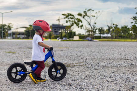 Adorable Asian kid boy (Toddler age 1-year-old), Wearing a Safety Helmet and Learning to Ride a Balance Bike in the Play Space. Baby Playground and Safe Place Concept. Portrait Photo with Copy Space.
