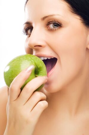 Young woman eating apple and smile over white background Stock Photo - 5011377