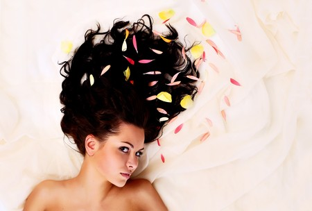 hair treatment: portrait of a young beautiful brunettes with long dark hair in the petals of flowers