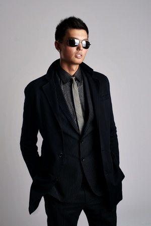 attractive young man wearing elegant black suit and sunglasses  Stock Photo