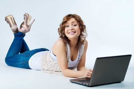 woman lying down: Woman lying on floor with laptop smiling