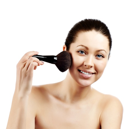 make up brush: Portrait of attractive young adult woman applying blusher