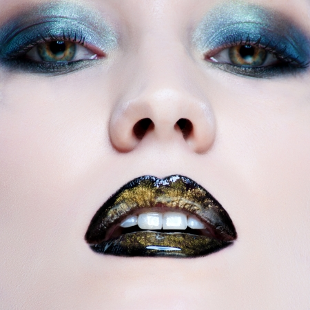 Close-up portrait of beautiful caucasian young woman with pearl glamour make-up and black lips photo