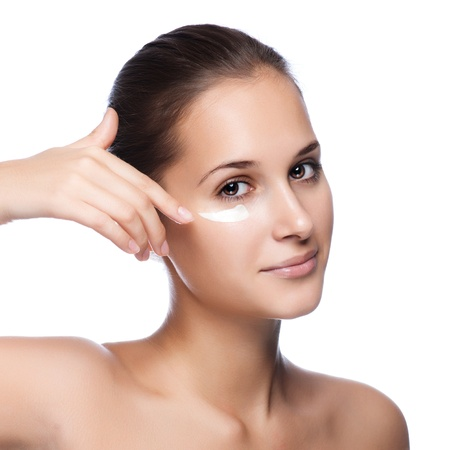 Portrait of beautiful woman applying cream on face - isolated on white  photo