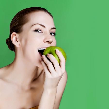 Femme mangeant la pomme souriant sur fond vert. Saine alimentation femme candide.
