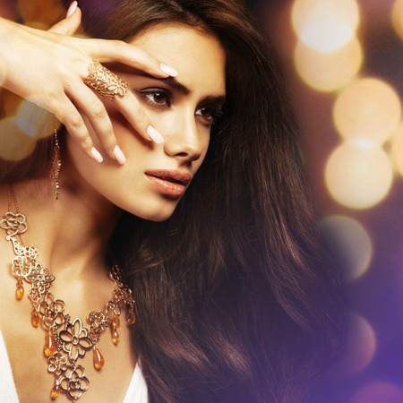 Beautiful young woman with long hair and jewelery.