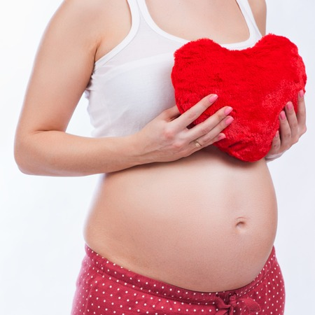 gynaecology: Pregnant mother showing her belly and holding a toy