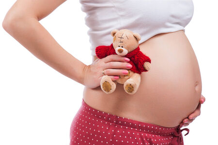 Pregnant mother showing her belly and holding a teddy Stock Photo