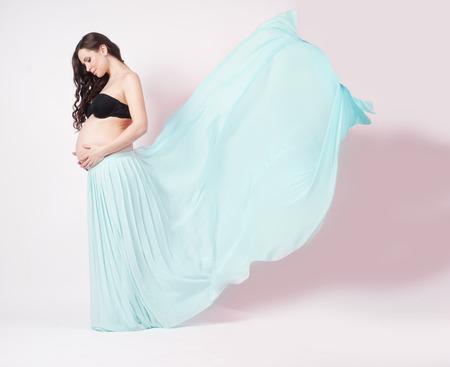 Portrait of a beautiful pregnant woman in blue chiffon shawl photo