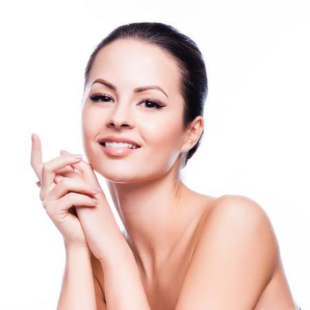 piel: Mujer hermosa joven que toca su Skin.Isolated Face.Fresh sano en blanco
