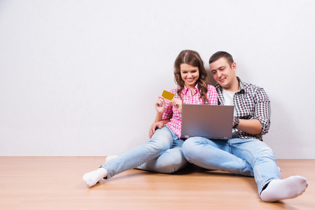 shopping online: Shopping online together. Beautiful young loving couple shopping online while sitting on the floore together