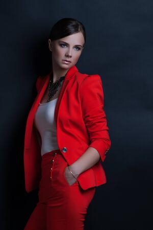 Portrait of a sexy young business lady in a red suit on a dark background photo