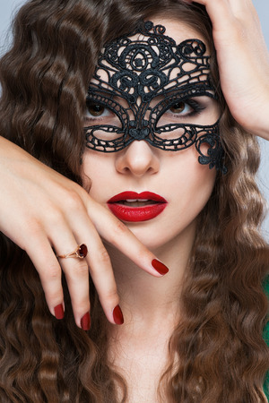 venetian: Beauty model woman wearing venetian masquerade carnival mask at party over holiday dark background with magic stars. Christmas and New Year celebration. Glamour lady