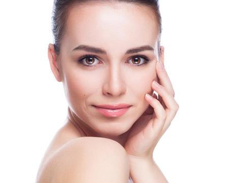 schoonheid: Mooie jonge vrouw wat betreft haar Face.Fresh Gezonde Skin.Isolated op Wit Stockfoto