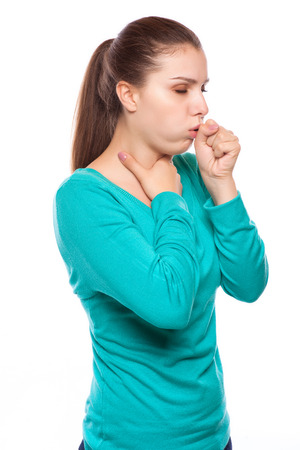 portrait of an young woman coughing with fist