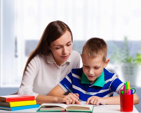 tarea escolar: Madre joven sentado en una mesa en casa ayudando a su pequeño hijo con su tarea de la escuela como escribe notas en un cuaderno