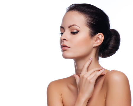 Belle jeune femme qui touche son visage. Peau saine et fraîche. Fabriqué sur le blanc