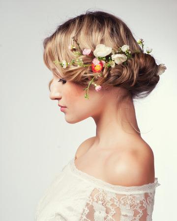 Schönes Mädchen mit Blumen im Haar. Frühling.