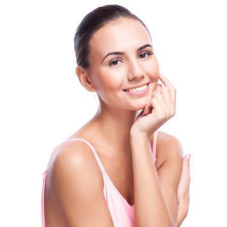 productos de belleza: Mujer hermosa joven que toca su Skin.Isolated Face.Fresh sano en blanco