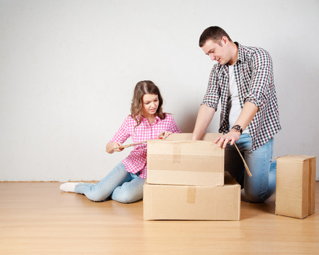 couple home: Happy young couple unpacking or packing boxes and moving into a new home.