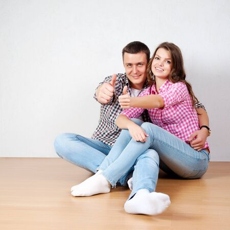 Beautiful barefoot young couple in casual jeans sitting leaning against a white wall on the wooden floor in the living room smiling at the camera