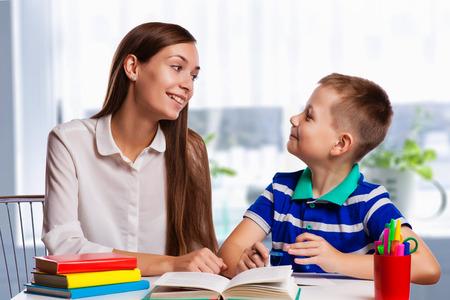 Jonge moeder zit aan een tafel thuis helpen haar zoon met zijn huiswerk van school zoals hij schrijft notities in een notitieblok Stockfoto - 41243035