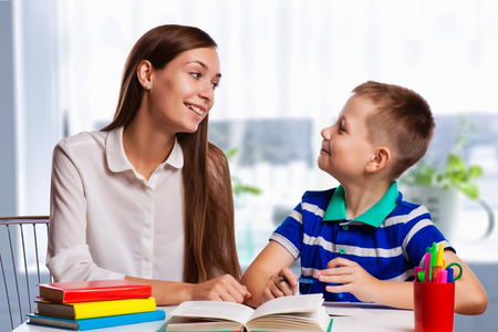 deberes: Madre joven sentado en una mesa en casa ayudando a su pequeño hijo con su tarea de la escuela como escribe notas en un cuaderno