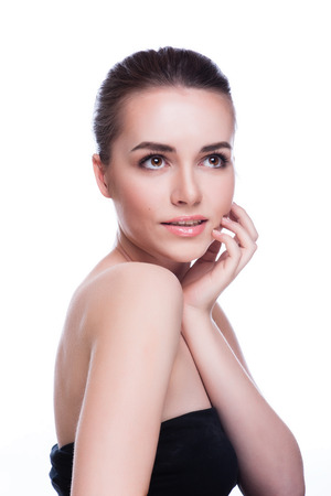 Mooie jonge vrouw aan haar gezicht te raken. Verse gezonde huid. Geïsoleerd op wit
