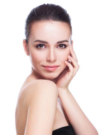 Mooie jonge vrouw wat betreft haar Face.Fresh Gezonde Skin.Isolated op Wit Stockfoto