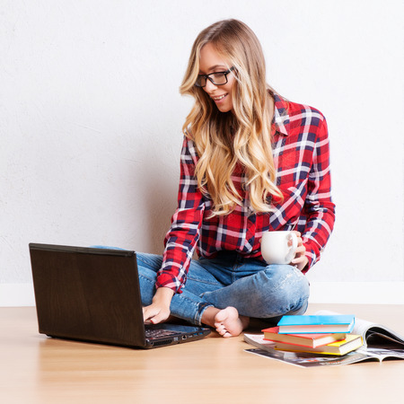 Junge kreative Frau sitzt auf dem Boden mit Laptop.  Casual Blogger Frau