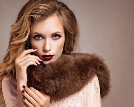 Mujer hermosa en abrigo de pieles de lujo
