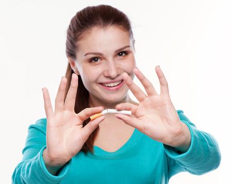 person smoking: Joven mujer feliz con el cigarrillo roto. Deje de fumar concepto.