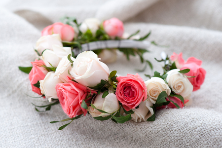 nude bride: tiara of artificial roses on wooden background.