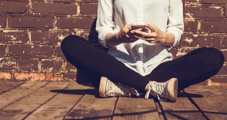 Piękna młoda kobieta hipster z wykorzystaniem inteligentnych telefonów