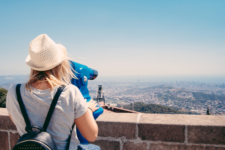 binoculars view: Young girl looking through a coin operated binoculars on the Barcelona