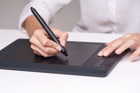 scribe: Closeup of female dressmaker sketching and drawing with graphic tablet. Horizontal shape, side view Stock Photo