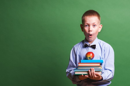 little boys: Happy little boy with books isolated on green background