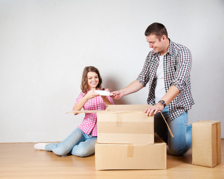 boite carton: Heureux jeune couple déballage ou de boîtes d'emballage et le déménagement dans une nouvelle maison. Banque d'images