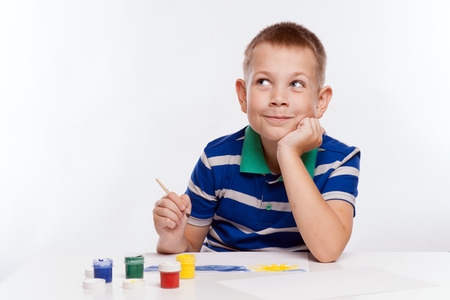 drawing boy: Happy cheerful child drawing with brush in album using a lot of painting tools. Creativity concept. Stock Photo