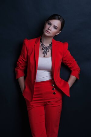 businesswoman suit: Portrait of a sexy young business lady in a red suit on a dark background Stock Photo