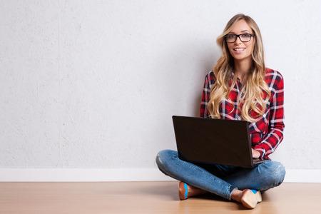 Jonge creatieve vrouw zitten in de vloer met de laptop.  Casual blogger vrouw Stockfoto