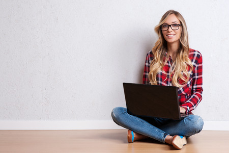 workspace: Young creative woman sitting in the floor with laptop. Casual blogger woman Stock Photo
