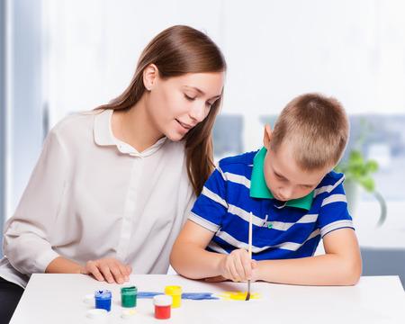 mama e hijo: Madre joven sentado en una mesa en casa ayudando a su hijo pequeño Foto de archivo