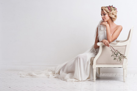 Schoonheid vrouw met huwelijks kapsel en make-up. Bruidsmode. Sieraden en schoonheidssalon. Vrouw in witte jurk, perfecte huid, blond haar. Meisje met stijlvolle kapsel. .Wedding Decoratie. Bruid met bloemen