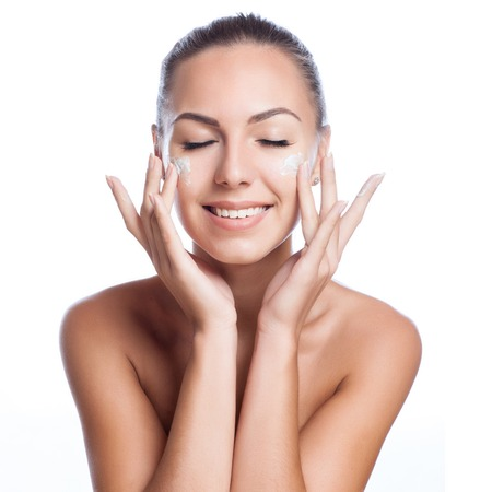 mujer maquillandose: bella modelo de aplicar el tratamiento crema cosmética en la cara en blanco Foto de archivo